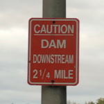 "Sign (at River) ""CAUTION DAM DOWNSTREAM 2/12 MILE"""