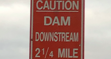"""Sign (at River) """"CAUTION DAM DOWNSTREAM 2/12 MILE"""""""