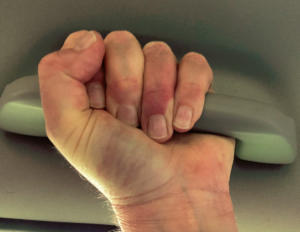 "Closeup of tightly clenched fist grasping ""grab handle"" in ceiling of car"